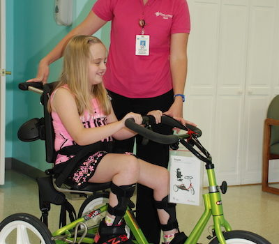 Therapist standing by child on therapy bike